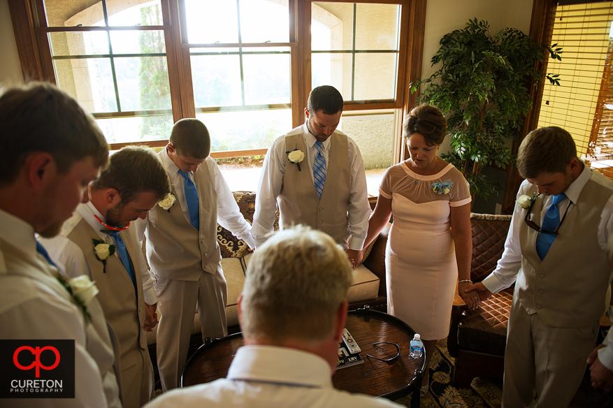 The groomsmen praying pre-wedding.