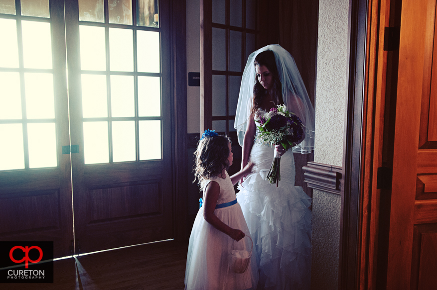 The bride talks to the flower girl pre-wedding.
