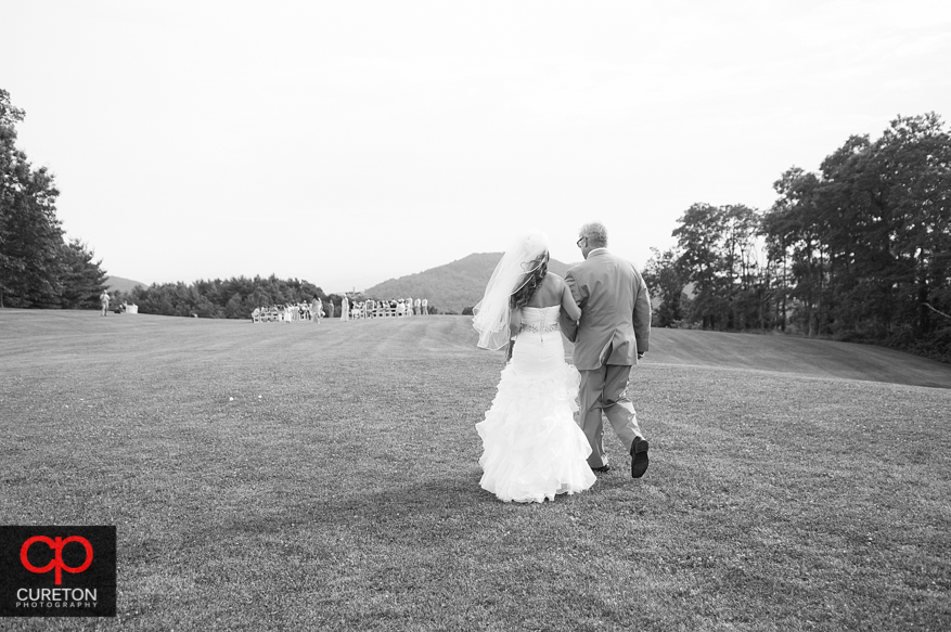 The father of eth bride walks his daughter down the aisle.