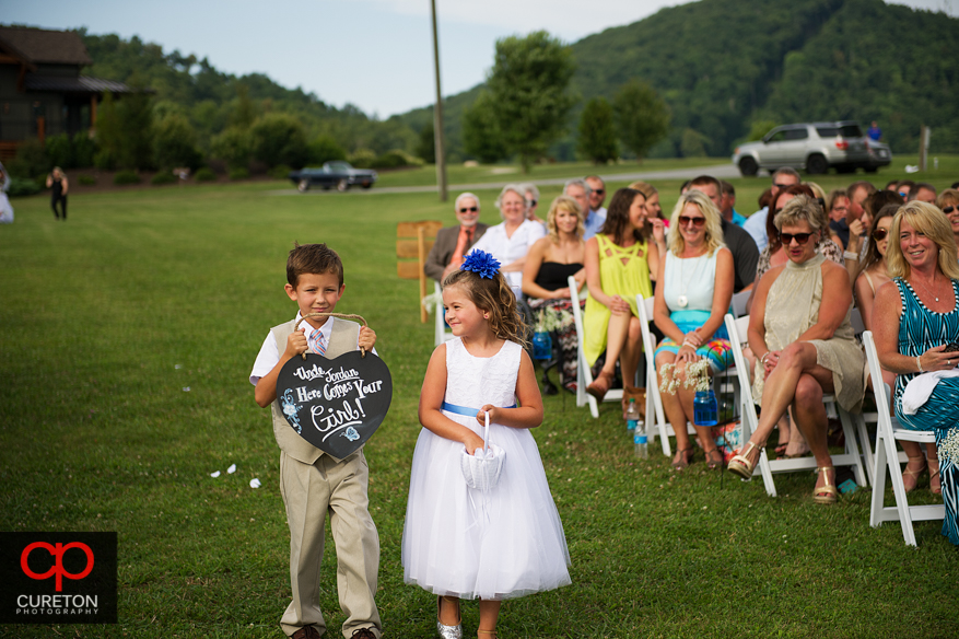 The cute flower girl looking at the ring bearer.