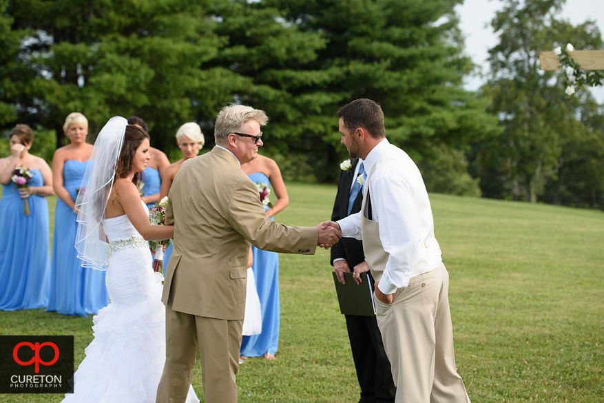 The groom shakes the bride's father's hand.