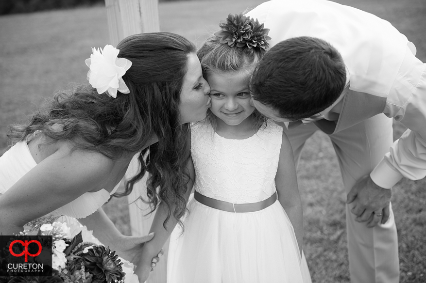 Bride and Groom kissing the flower girl.