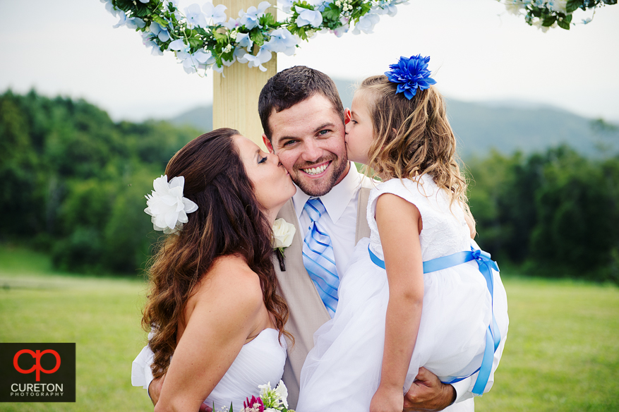 The groom getting kissed by his bride and daughter.