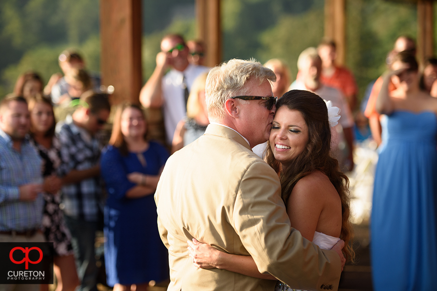 Bride dancing with her father on the patio.