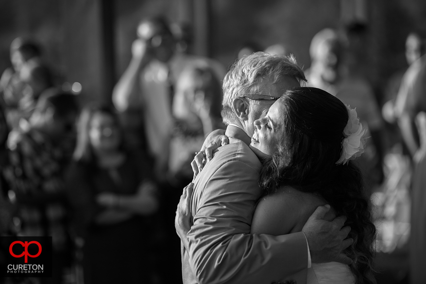 Bride hugs her father after their first dance.