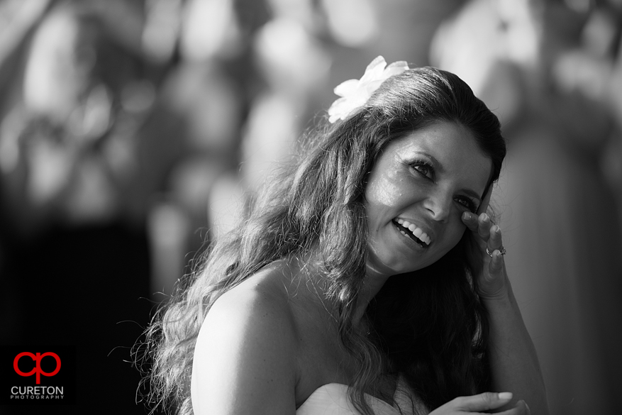 Bride wipes away tears from her face.