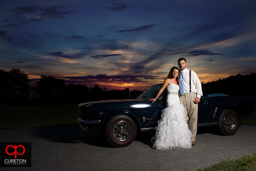Bride and Groom with vintage Ford Mustang at sunset in the mountains.