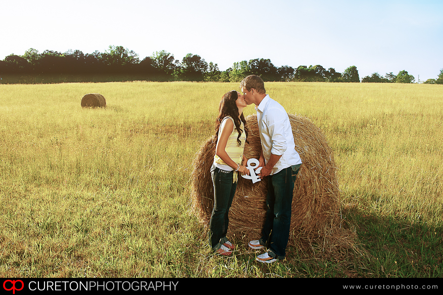 A couple in front of a hay bale at a Greenville farm.