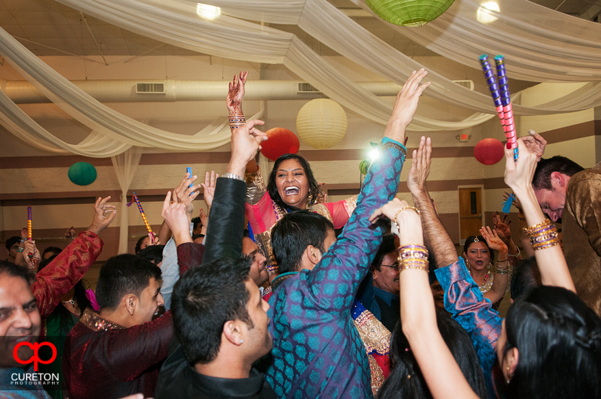 Bride is lifted up ob the shoulders of guests at the Garba party.