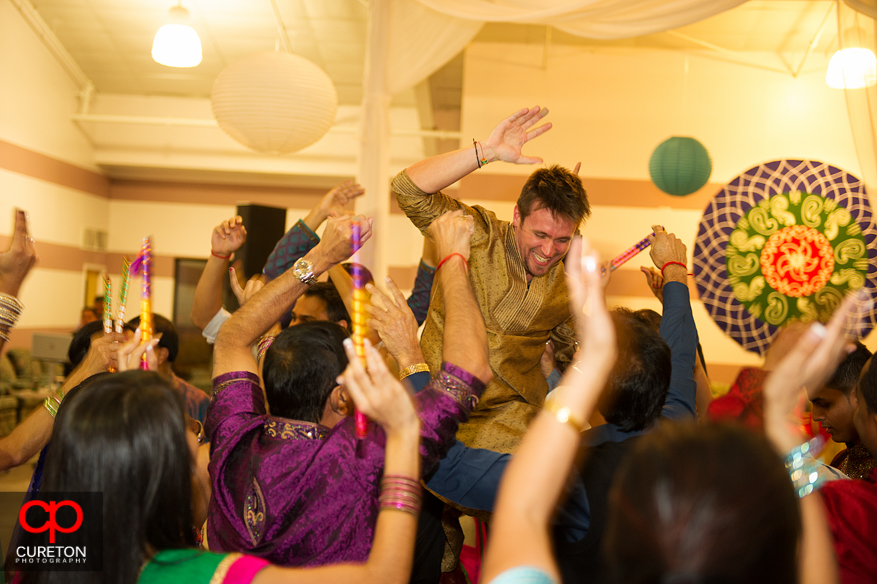Groom is lifted up on the shoulders of guests at Garba.