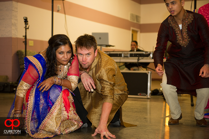 Bride and groom kneeling on the floor at the garb before their wedding.