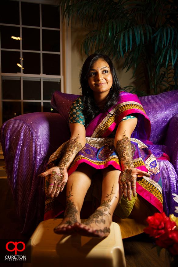 Indian bride sitting down displaying henna tattoos.