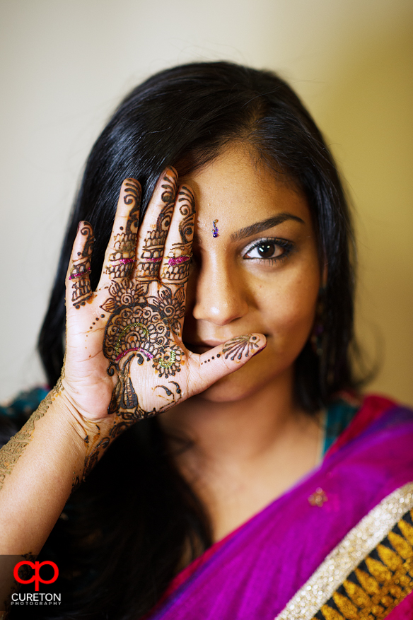 Bride with her henna covered hand in front of her face during her mehndi party in Greenville,SC.