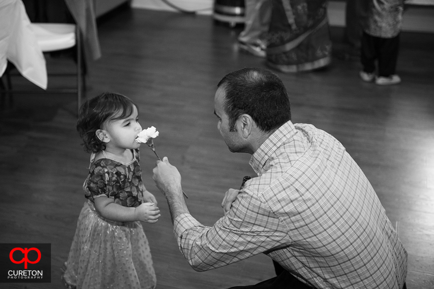 A dad gives flower to his daughter.