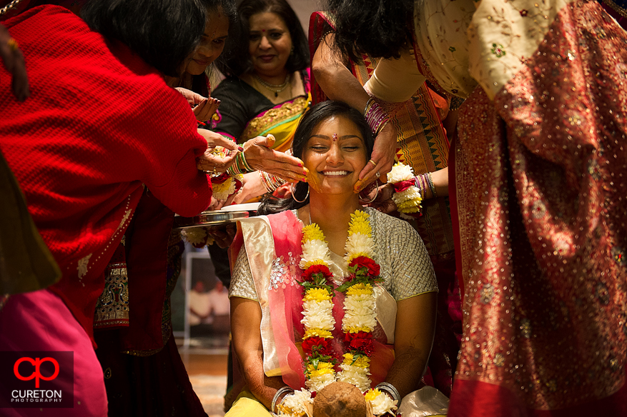 Indian bride getting turmeric paste applied during her vidhi in Greenville,SC.