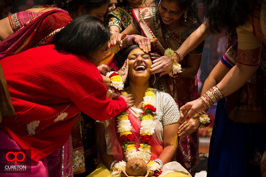 Indian bride getting turmeric paste applied by her family during her vidhi in Greenville,SC.