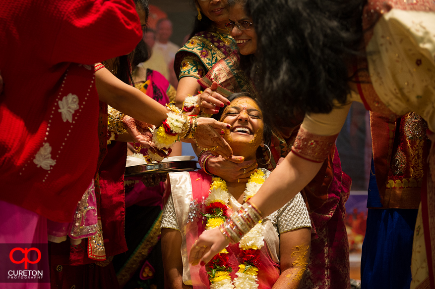 Indian bride with family and bridesmaids putting turmeric paste on her during her vidhi in Greenville,SC.