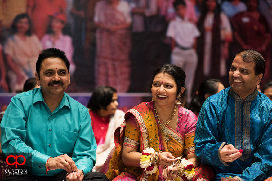 Brides family and bridesmaid smiling during the vidhi.