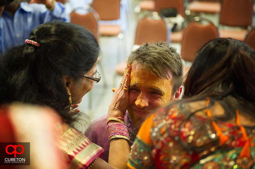 The groom is surprised with turmeric paste.