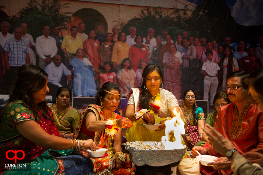 An Indian bride places items in the fire during her vidhi ceremony.