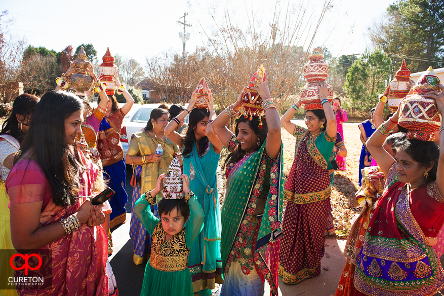 Indian bridesmaids walk with pots on their heads.