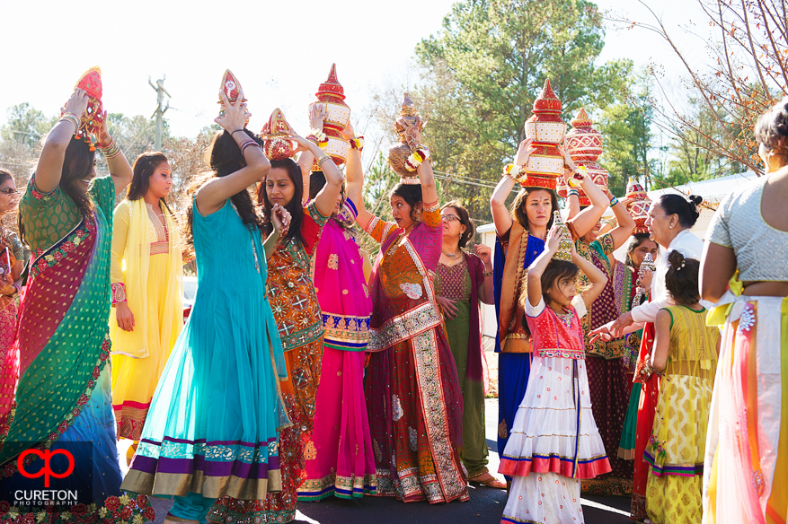 Indian women walk with pots on their heads during a traditional vidhi ceremony.