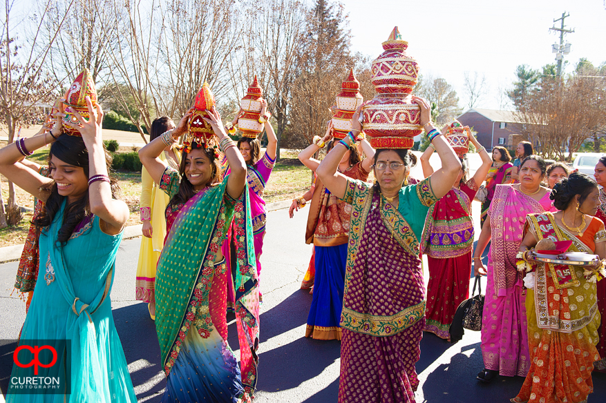 Indian women walking with pots on their heads at the end of a traditional Indian vidhi ceremony.
