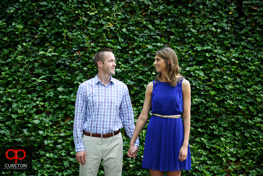 Engaged couple standing in front of a wall of ivy in Falls Park in Greenville,SC.