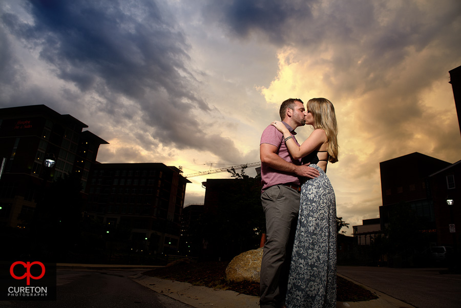 Couple kissing at sunset during a downtown Greenville engagement session.