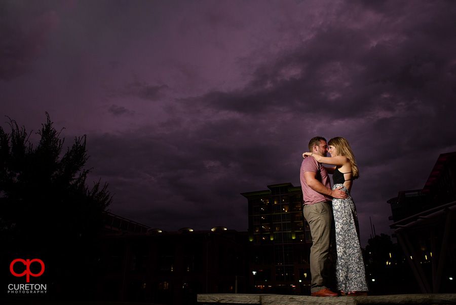 Engaged couple dancing under purple skies in downtown Greenville,SC.