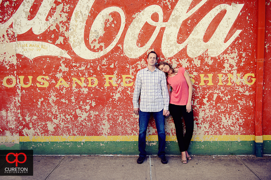 Engaged couple standing in front of the painted Coca Cola wall in downtown Greenville,SC.