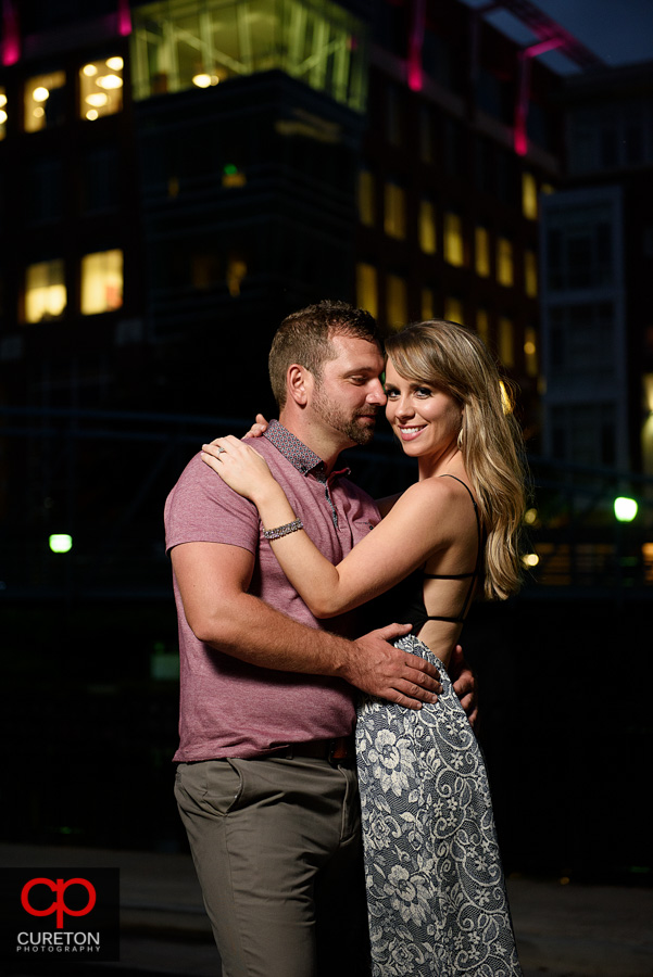 Engaged couple dancing at dusk in downtown Greenville during an engagement session.
