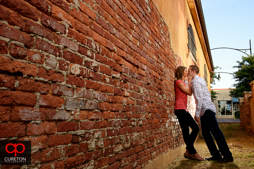 Engaged couple kissing in an alleyway.