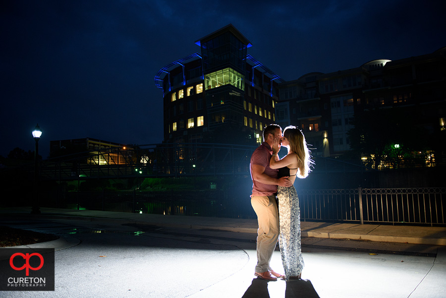 Backlit epic engagement photo with the city lights backdrop.