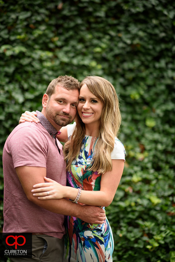 Engaged couple near a wall of ivy.