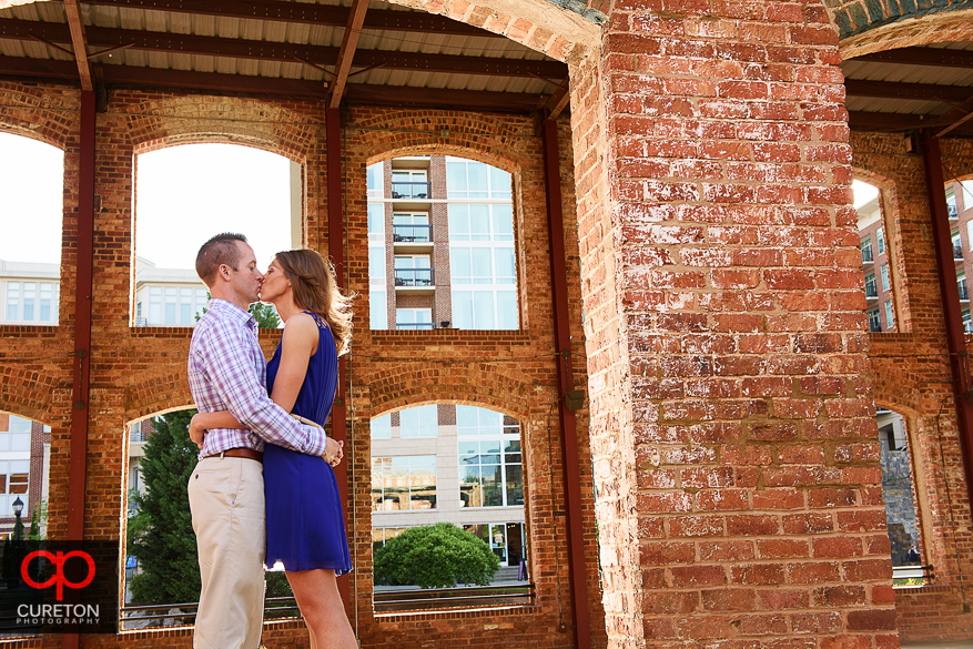 Bride and groom to be kissing at the Wyche Pavilion during a pre wedding session in downtown Greenville,SC.