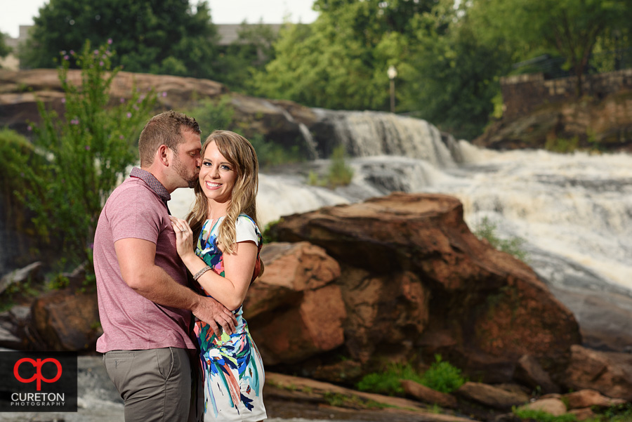 Engaged couple kissing at the waterfall.