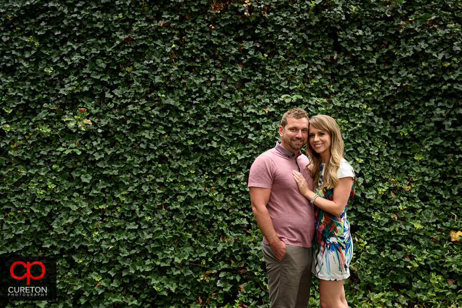 Engaged couple posing in front of a wall of ivy.