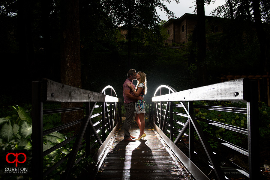 Couple walking across a small bridge in the park.