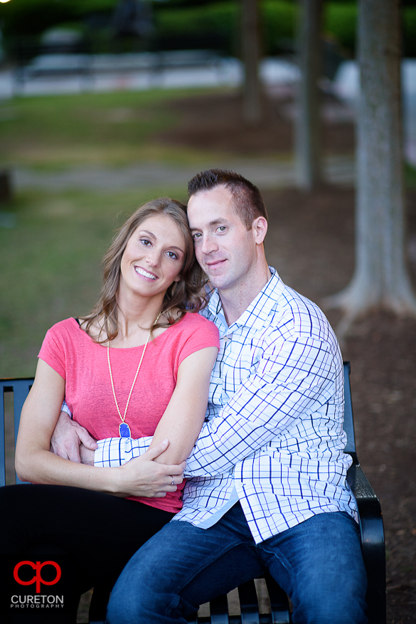 Engaged couple sitting on a bench in downtown Greenville.