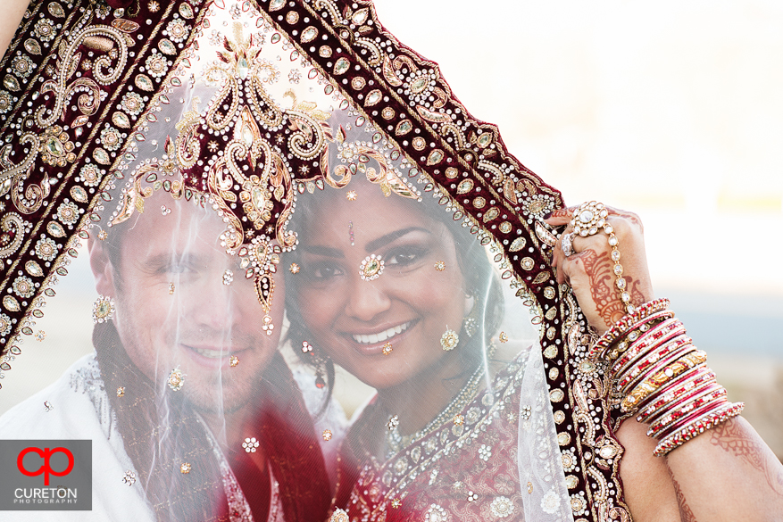 Couple looking through brides veil outside their Indian wedding in Greenville,SC..