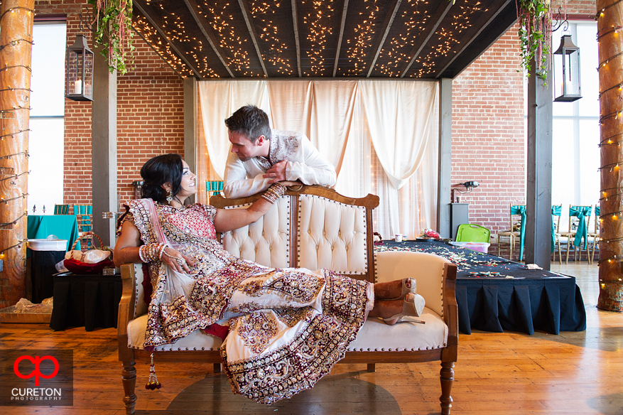Bride and groom sit on a couch before their wedding.