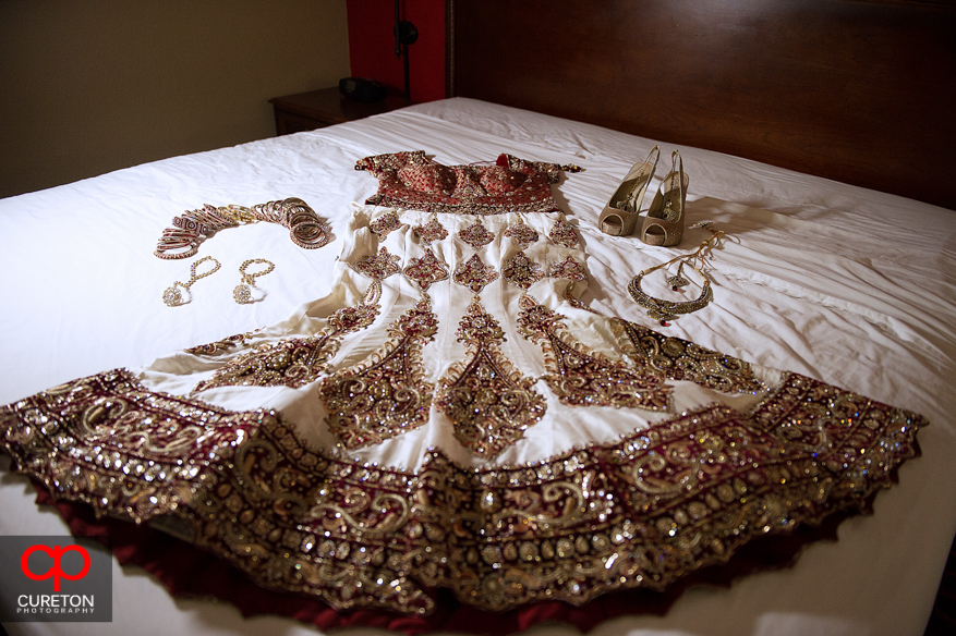 Indian bridal dress laid on a bed/