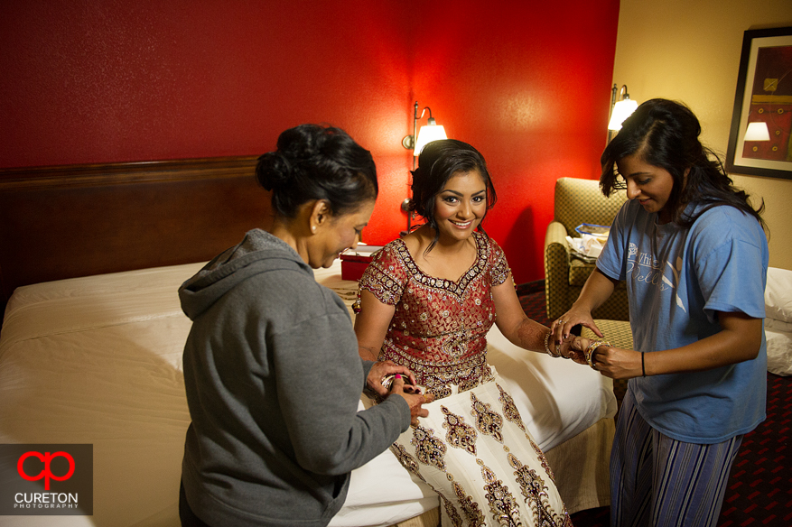 Brides mom and cousin help her get ready before her Indian wedding in Greenville,SC.