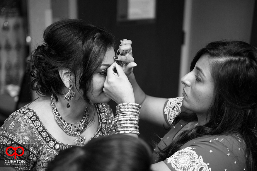 Bride's sister helping the bride get ready.