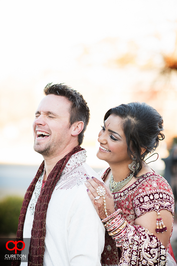 Groom laughing with bride during their first look.