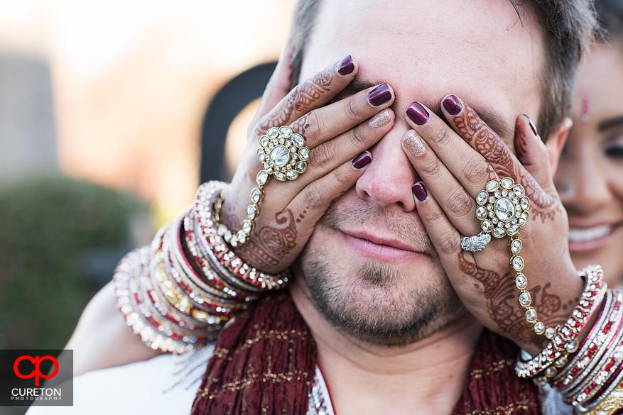 Bride covering grooms eyes showing her elaborate jewelry,