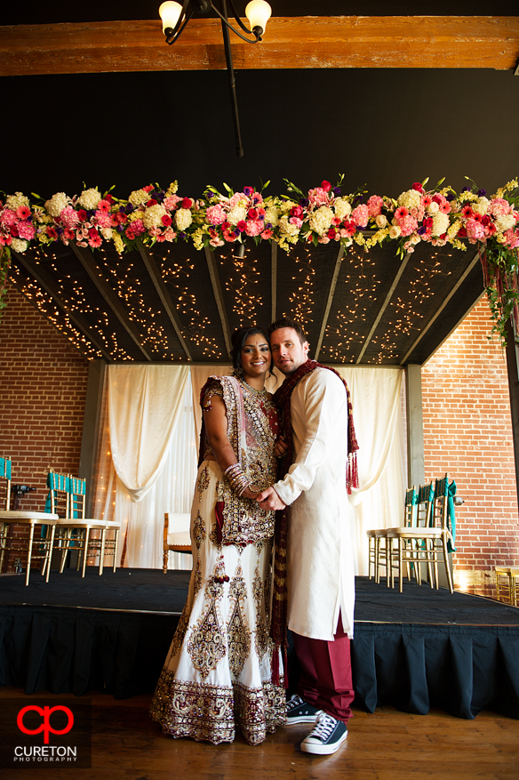 Groom and bride stand under the mandap their Indian wedding in Greenville,SC..