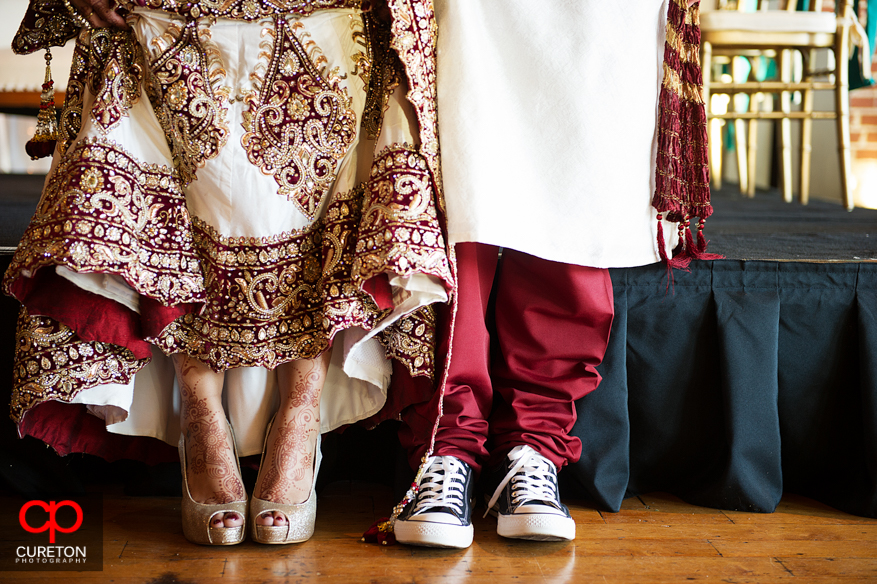 Groom and bride showing their shoes.