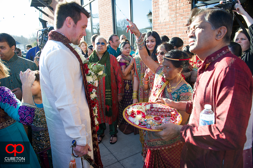 Bride;s mother greets the groom at the door during traditional Indian wedding.